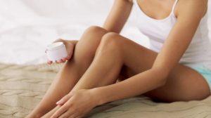γυναίκα βάζει ενυδατική κρέμα πόδια