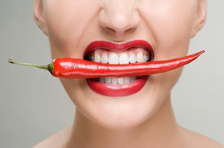 γυναίκα δαγκώνει κόκκινη πιπεριά