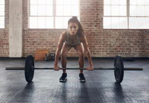 γυναίκα σηκώνει μπάρα βάρη βελτιώσεις μεταβολισμό