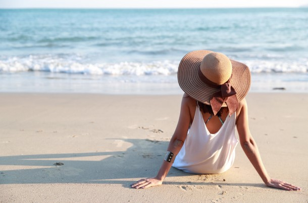 κοπέλα κάθεται άμμο καπέλο