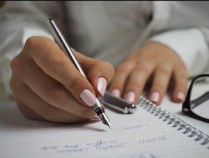 γυναίκα γράφει σημειωματάριο