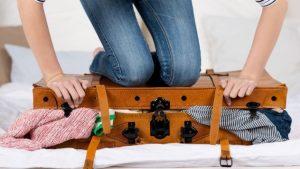 γυναίκα κλείνει γεμάτη βαλίτσα