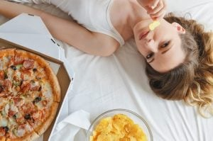 γυναίκα τρώει πίτσα πατατάκια κρεβάτι