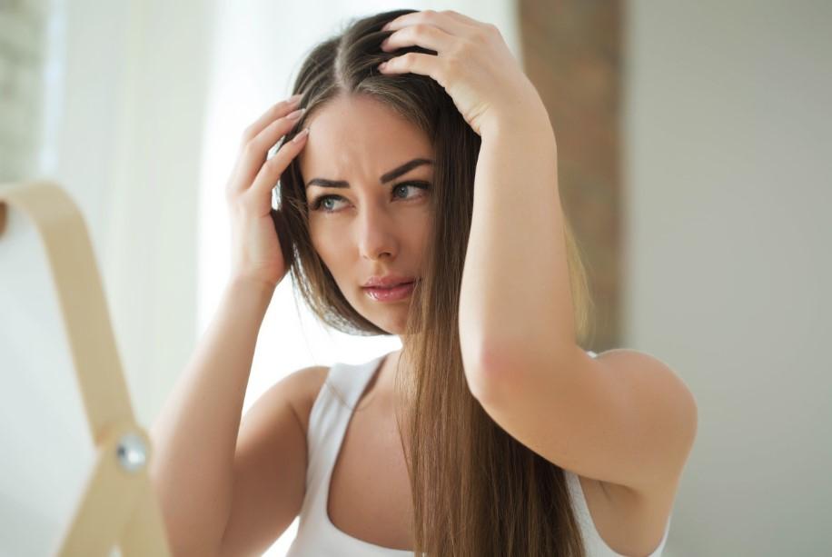γυναίκα κοιτάει τη ρίζα των μαλλιών της