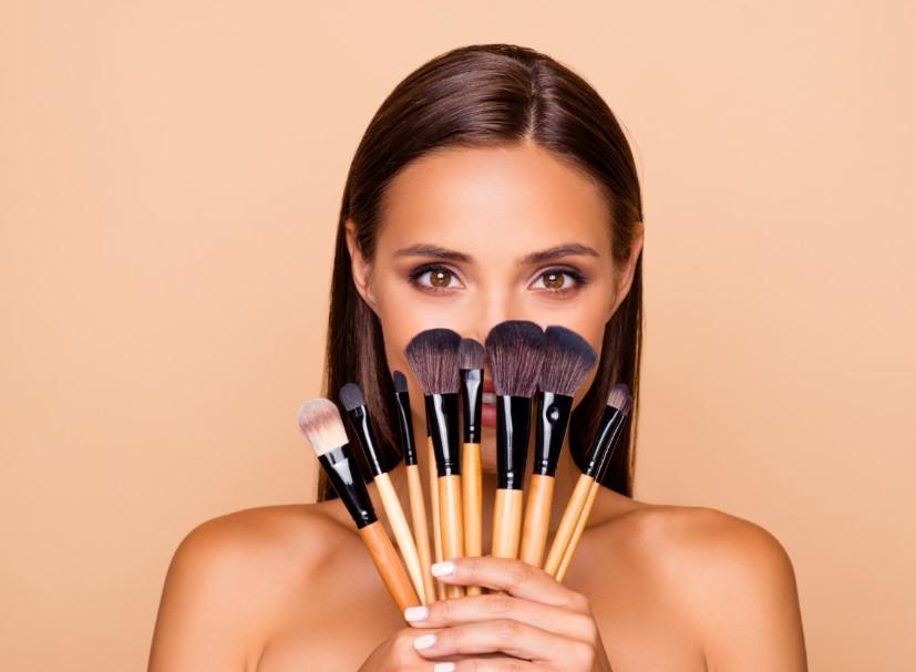 γυναίκα κρατάει πινέλα μακιγιάζ