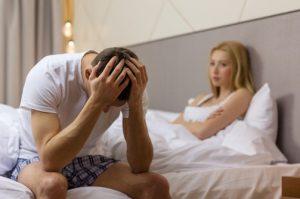 άντρας κάθεται απογοητευμένος στο κρεβάτι