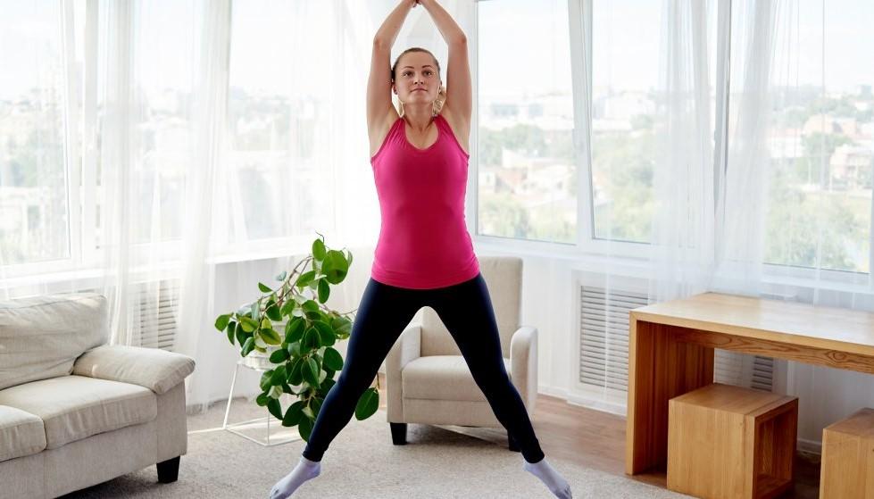 γυναίκα κάνει jumping jacks σπίτι
