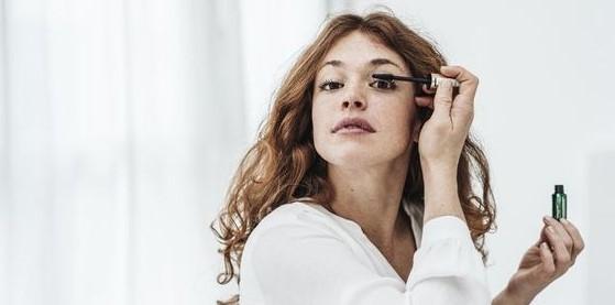γυναίκα βάζει μάσκαρα καλλυντικά νεσεσέρ