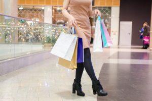 γυναίκα που κρατάει πολλές σακκούλες από ψώνια