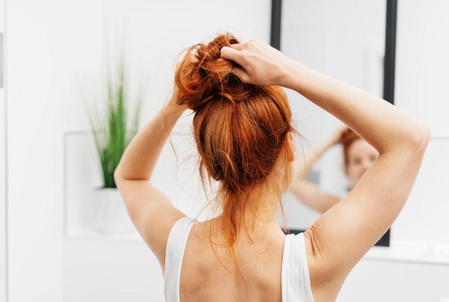 γυναίκα μαζεύει ψηλά τα μαλλιά της