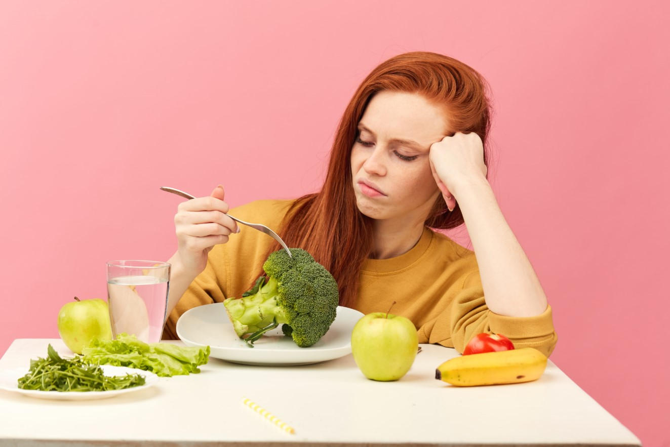 δυσαρεστημένη γυναίκα τρώει υγιεινά