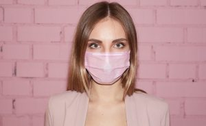 γυναίκα φοράει ροζ μάσκα σπυράκια