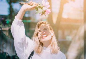 χαρούμενη γυναίκα με λουλούδια στον ήλιο