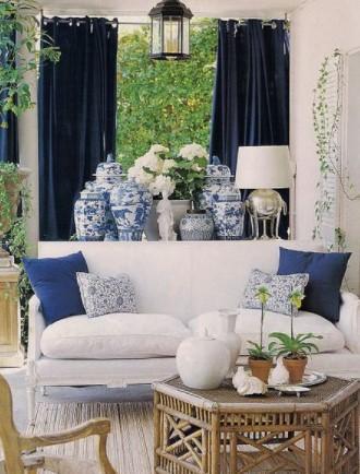 λευκός καναπές με μπλε μαξιλάρια και κουρτίνες