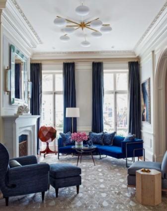 μπλε καναπές με σκούρη μπλε κουρτίνα