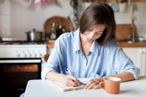 χαρούμενη γυναίκα γράφει