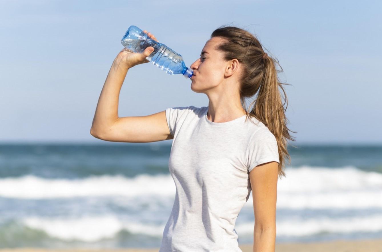 γυναίκα πίνει νερό στη παραλία